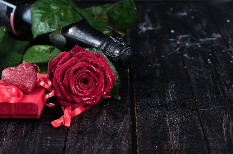 Valentine's day roses and champagne over dark background